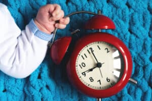 Baby hand with a red alarm clock laying on blue blanket