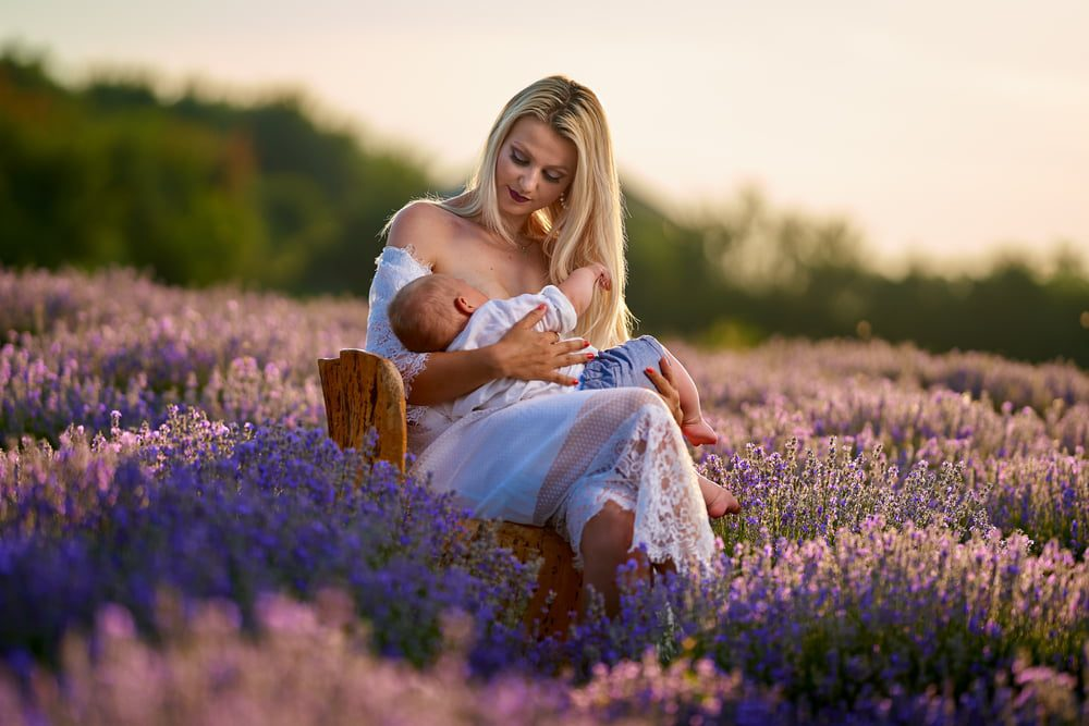 Mother breastfeeding her son in lavender field