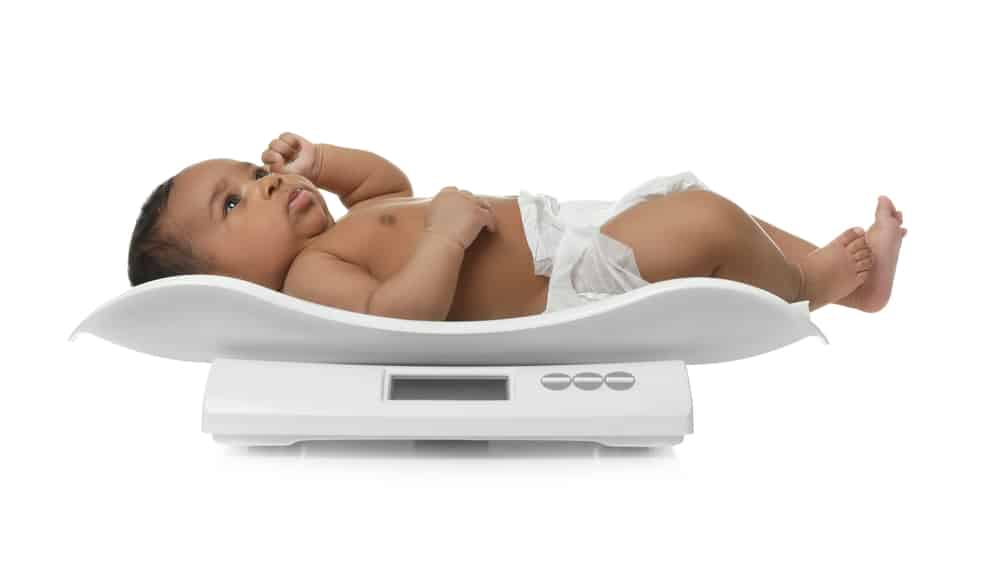 African-american baby lying on a scale