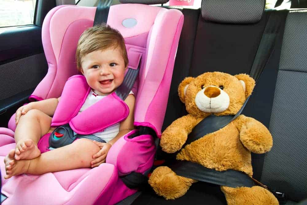 Baby girl in car seat and large teddy bear buckled in next to her
