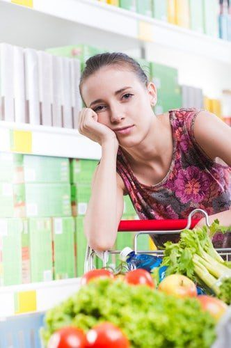 Young woman in grocery store with grocery cart