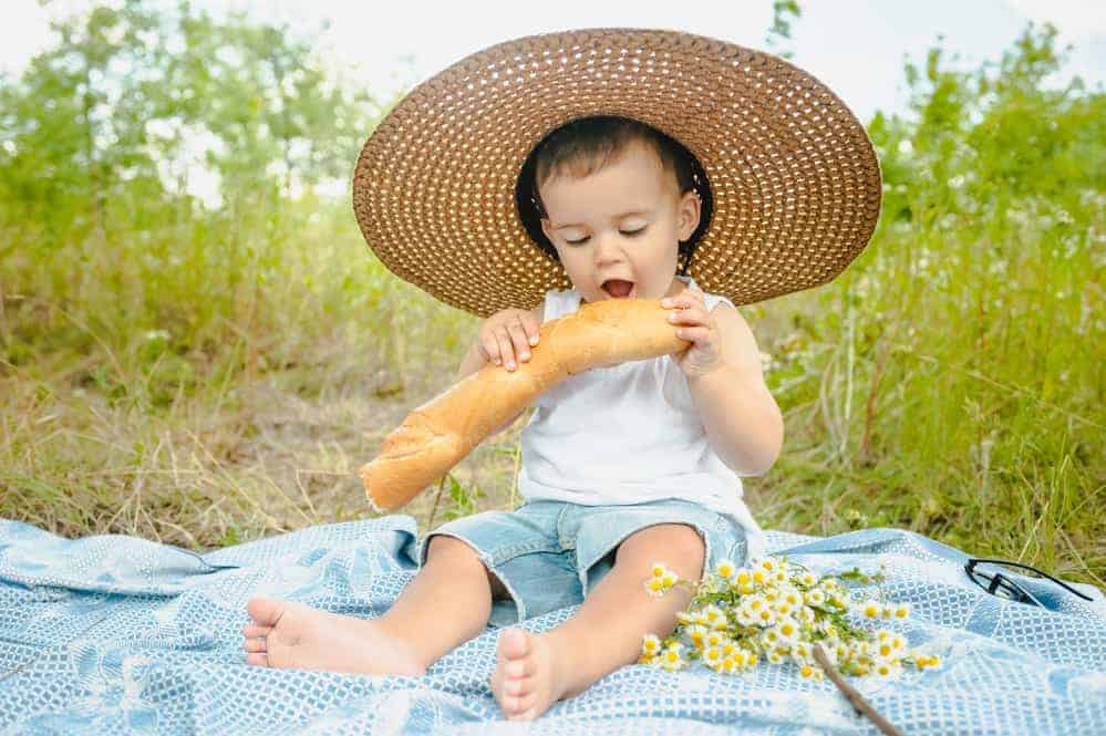 baby taking a bite from a baguette