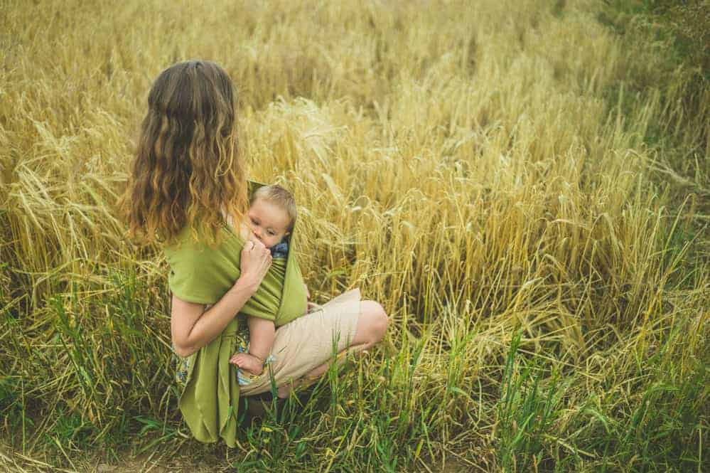 mother breastfeeding a baby with reflux out in a field in an upright position