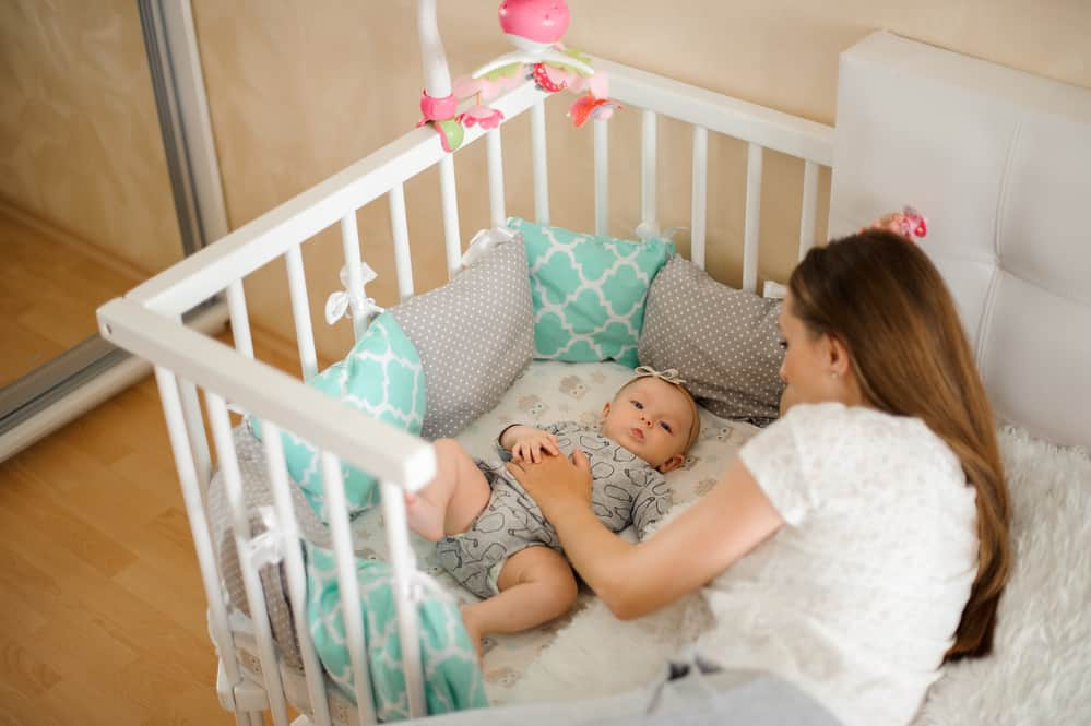Mother with baby in co-sleeper to ensure they are bedsharing safely