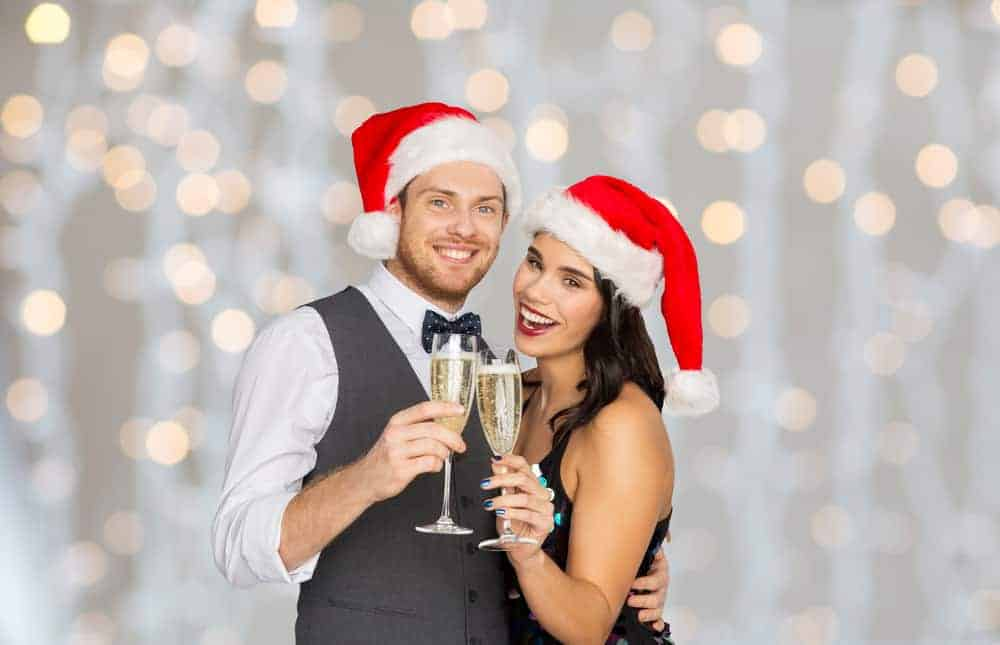 man and woman wearing santa hats holding flutes of champagne