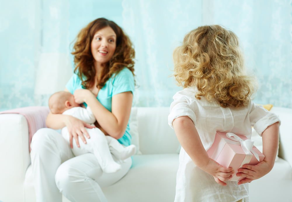 Mother breastfeeding and little girl holding a gift behind her back