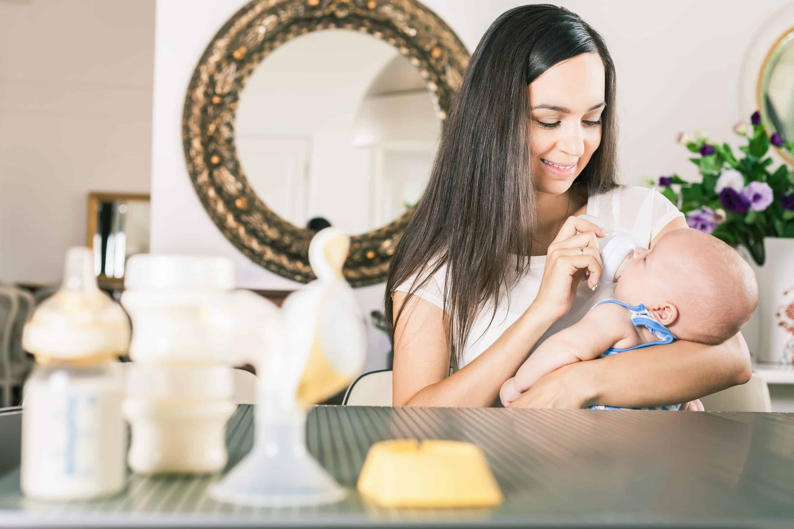 mother bottle-feeding baby with breast pump in foreground