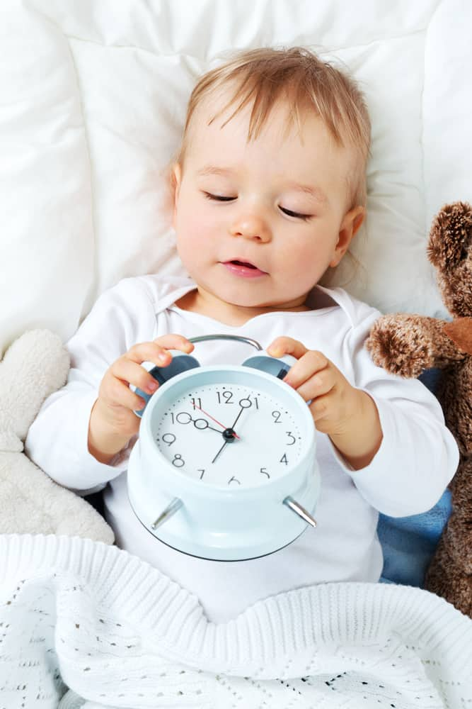 BABY HOLDING A BLUE CLOCK