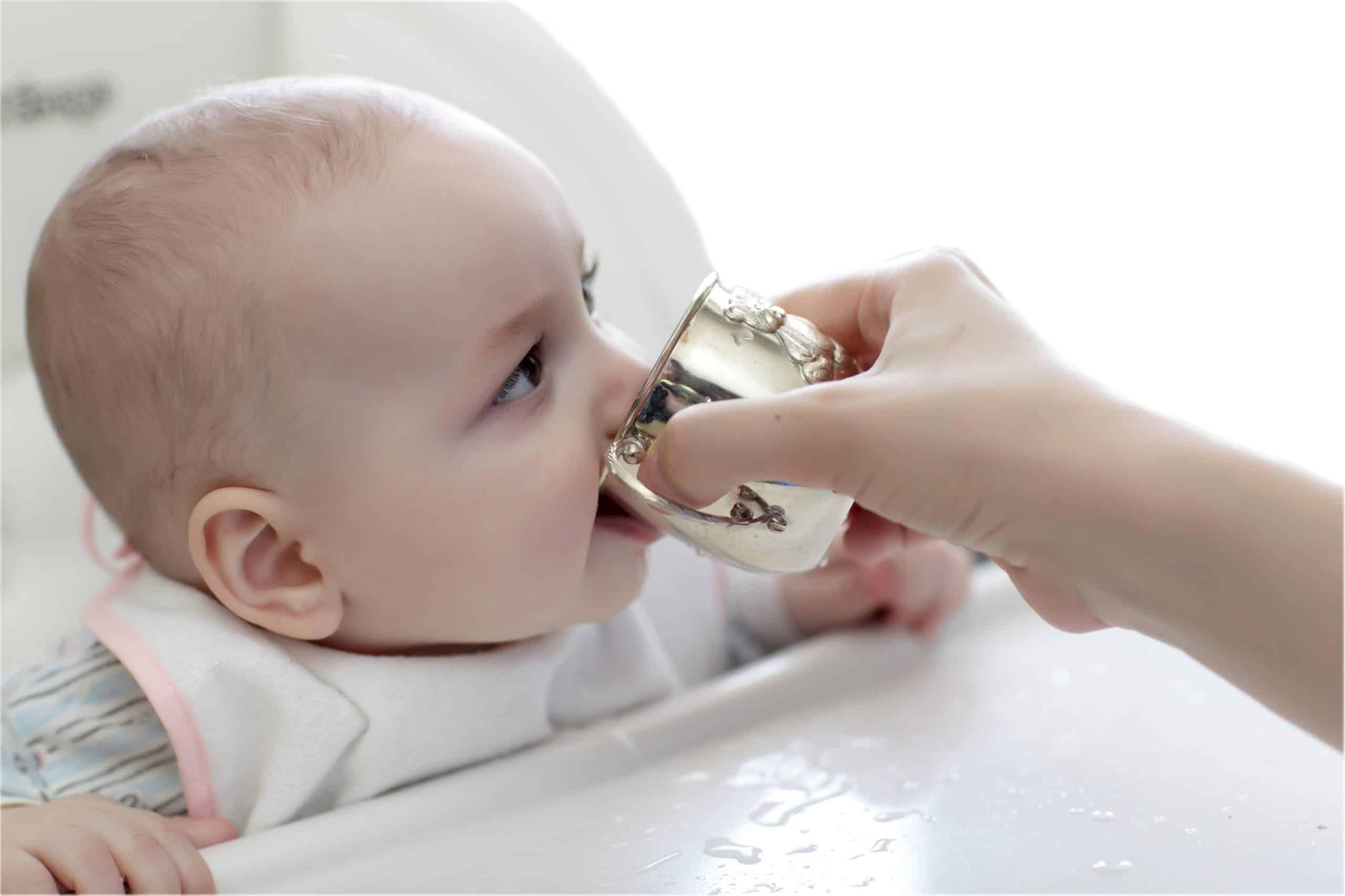 causcasian baby drinking from a cup