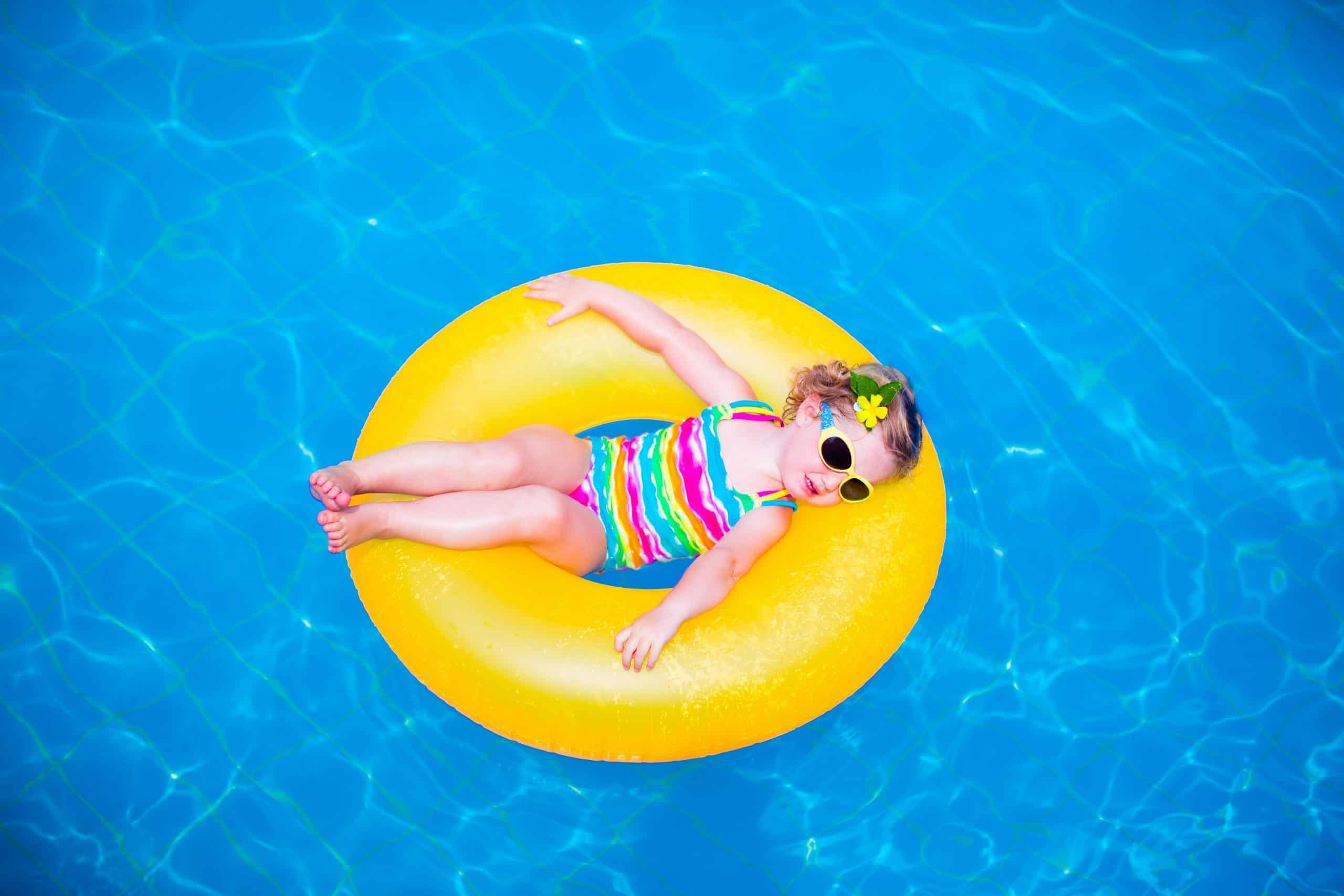 little girl in a swimming ring floatie in a swimming pool
