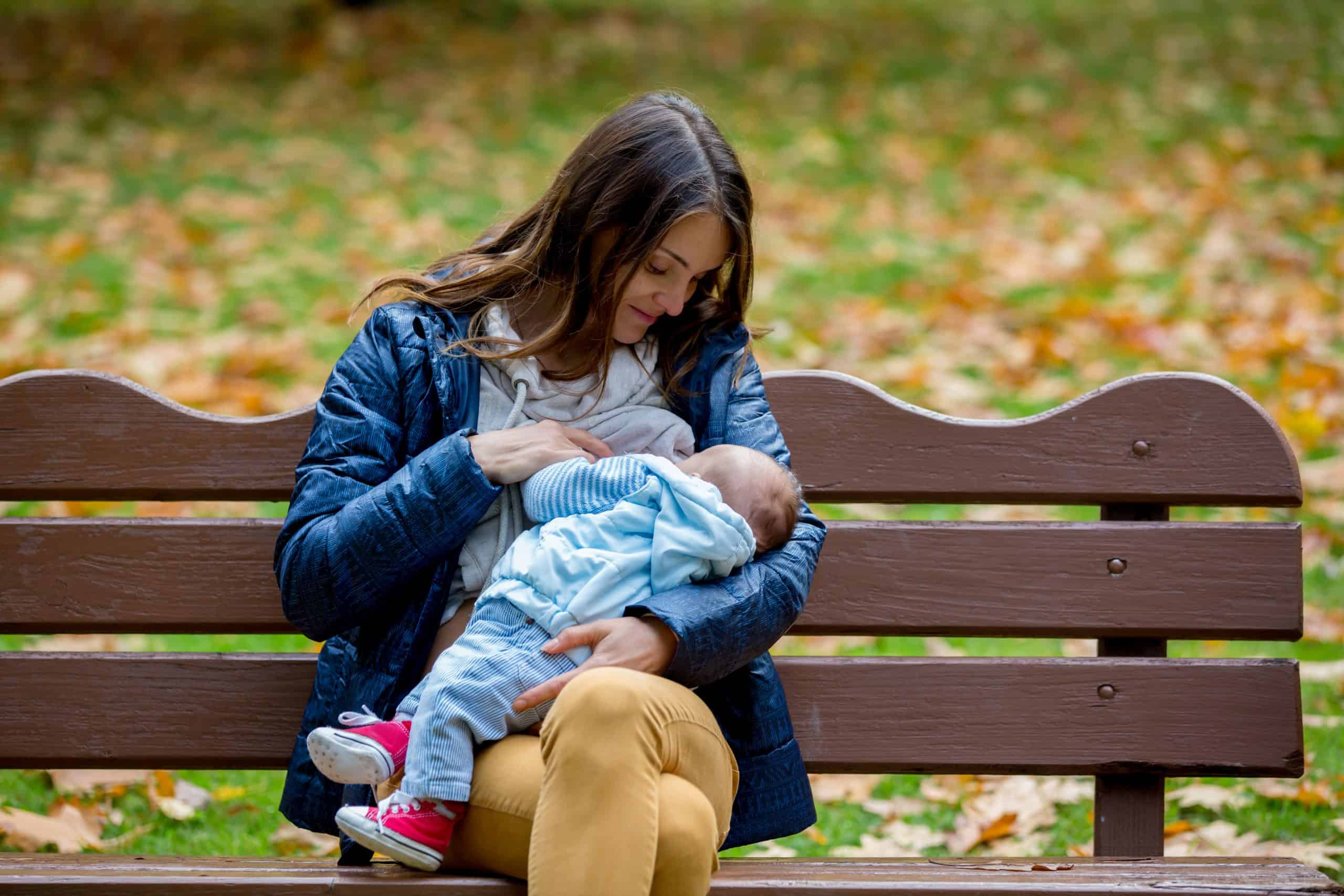 mother breastfeeding on a park bench outside
