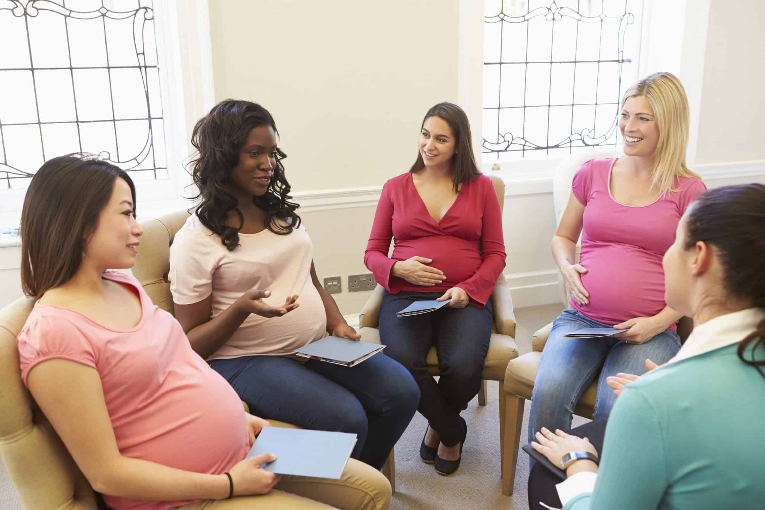 Five pregnant women sitting on chairs