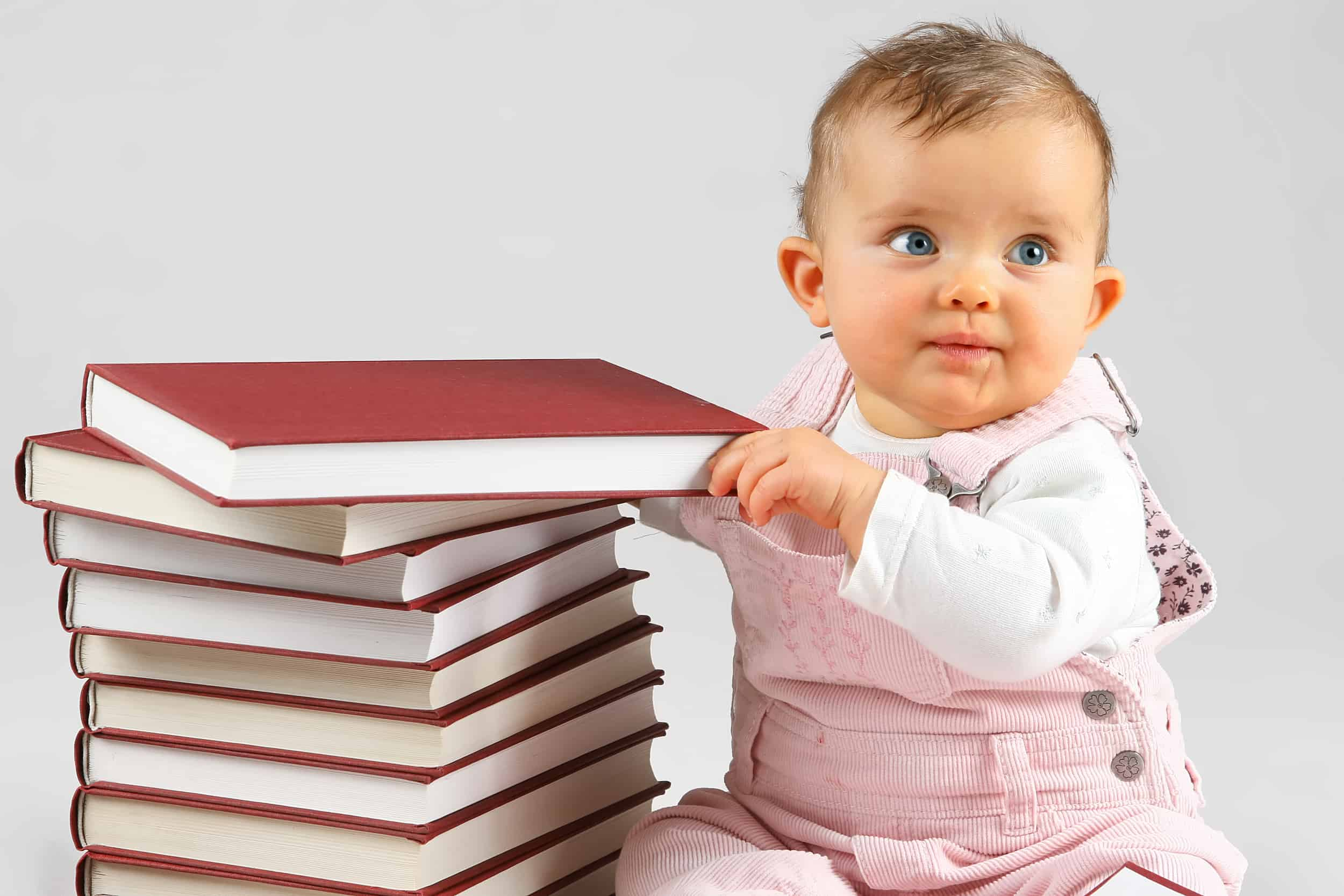 small baby girl and many red books with red cover