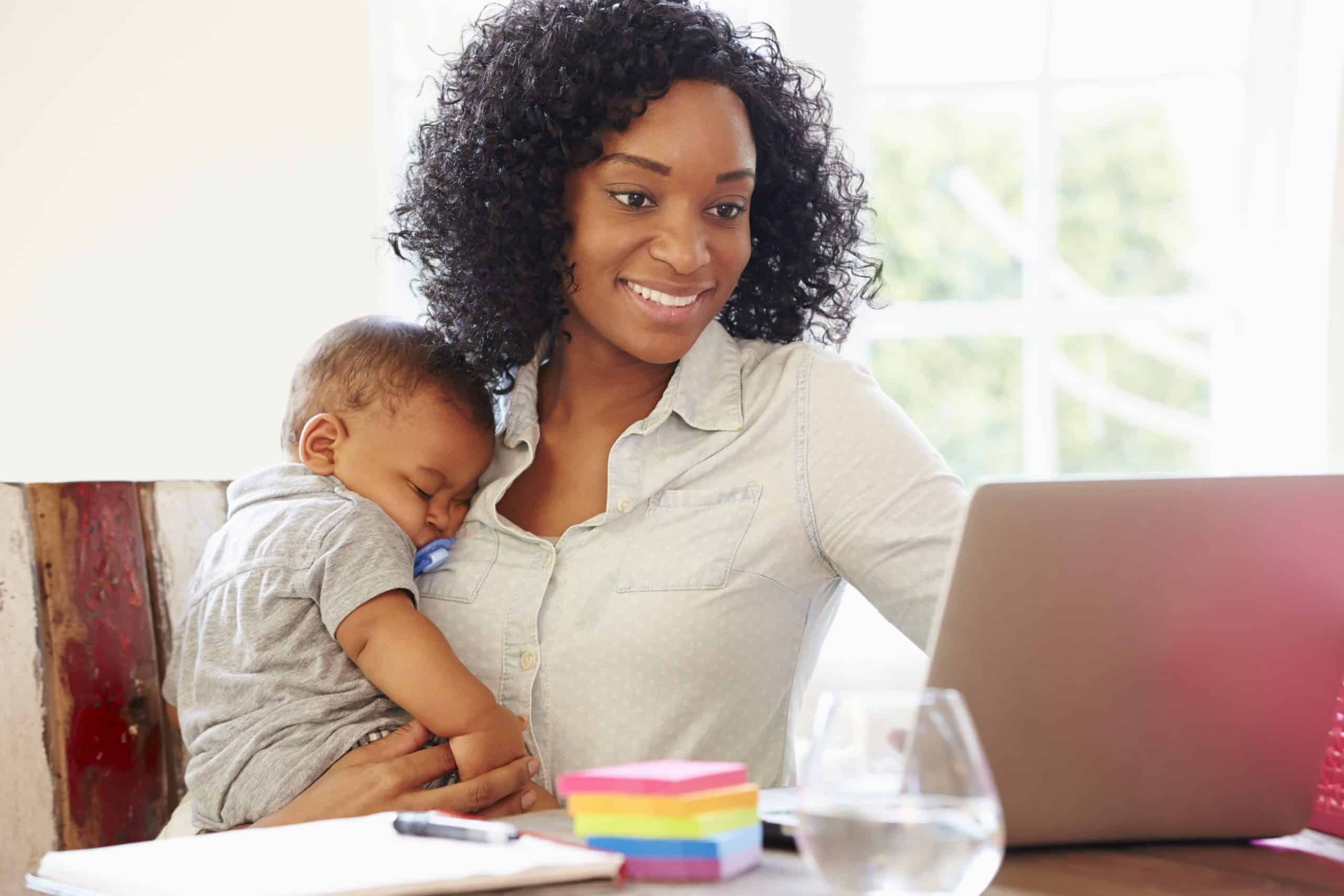 african american woman holding baby while she looks at her computer