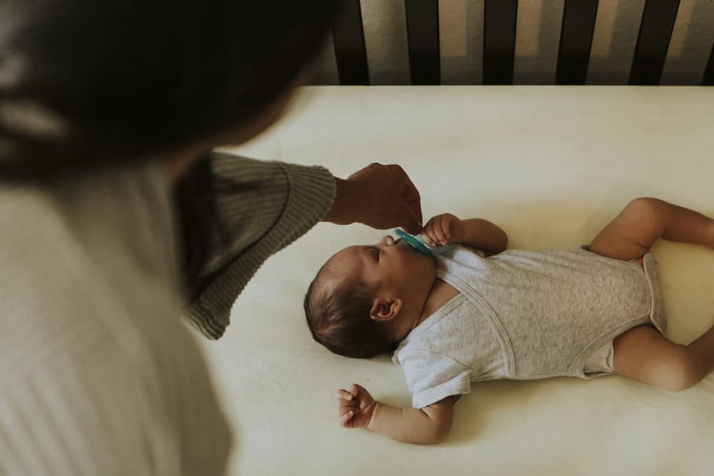 mother giving her baby a pacifier while he is in a crib