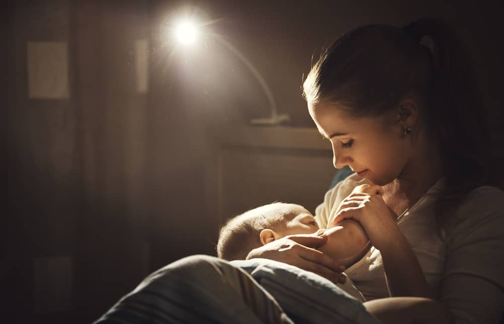breast-feeding. mother breastfeeds baby in dark in bed