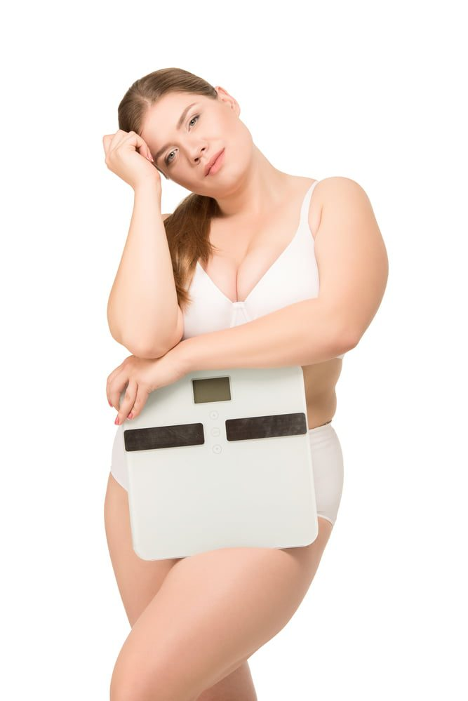 woman in white bra and panties holding a scale