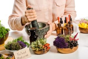person preparing herbs with a mortar and pestle