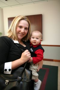 working mother holding baby and briefcase