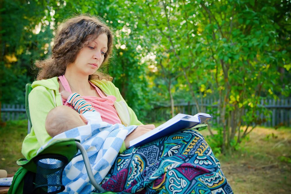 woman breastfeeding outside and reading a book