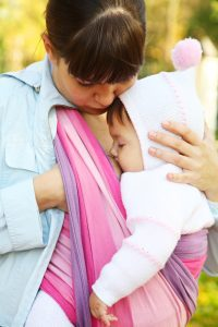 mother Breastfeeding child in a baby sling
