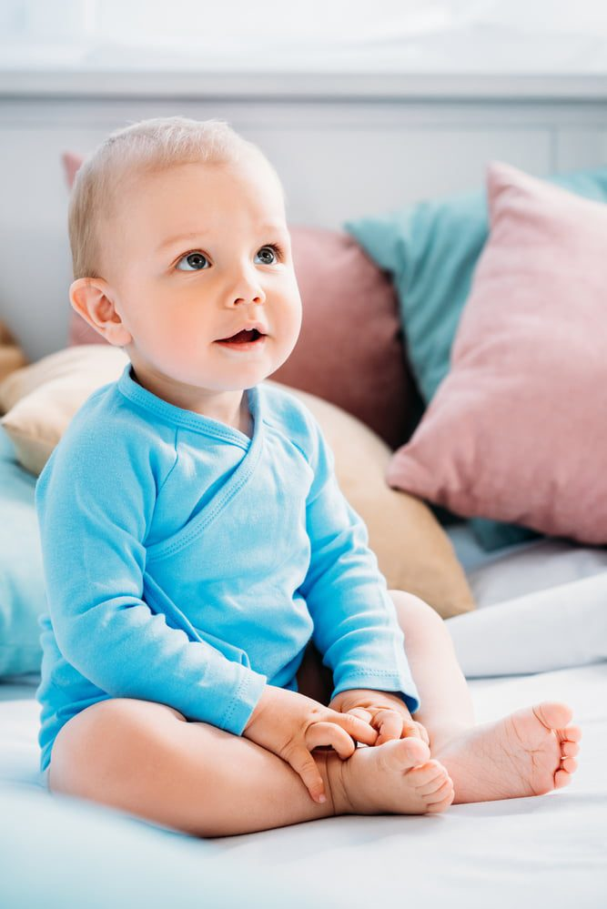 Baby in blue outfit sitting up looking up