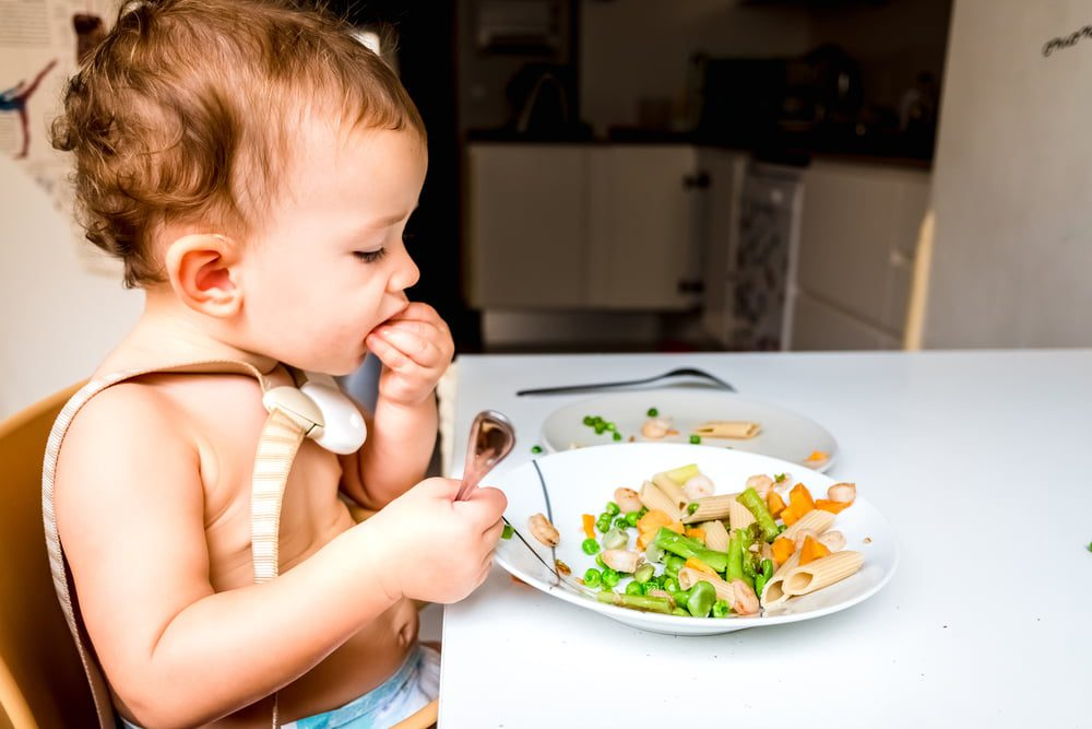 Baby sitting in high chair feeding himself pasta and vegetables