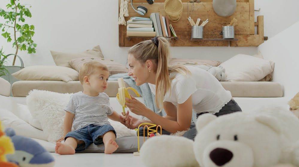 mother offering baby a banana